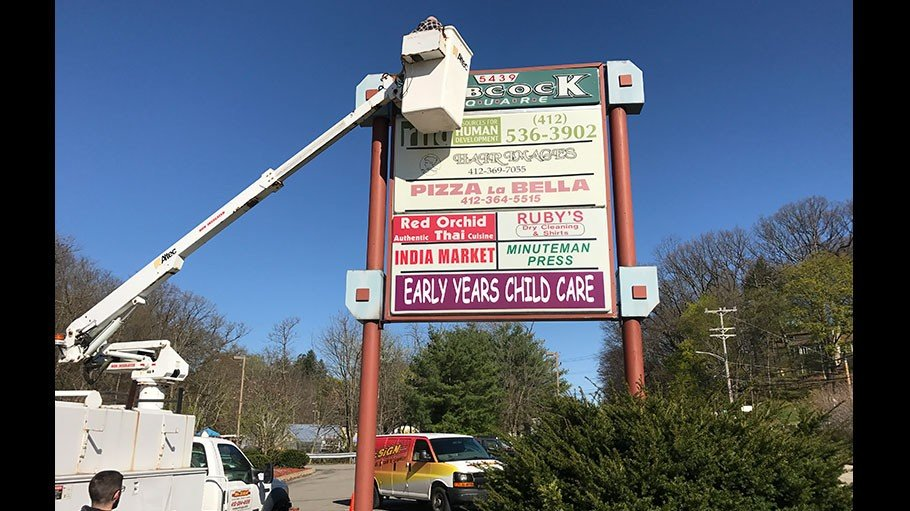 Company installing business sign in a plaza