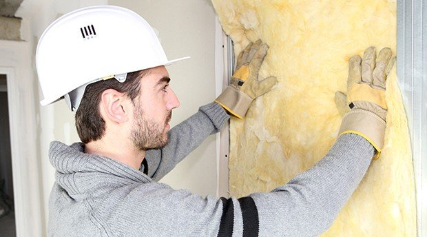 contractor installing insulation in a dry wall to prevent damage to client home