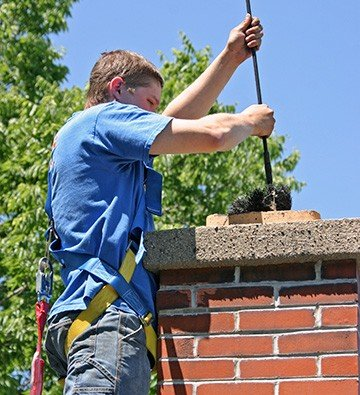 young contractor cleaning chimney